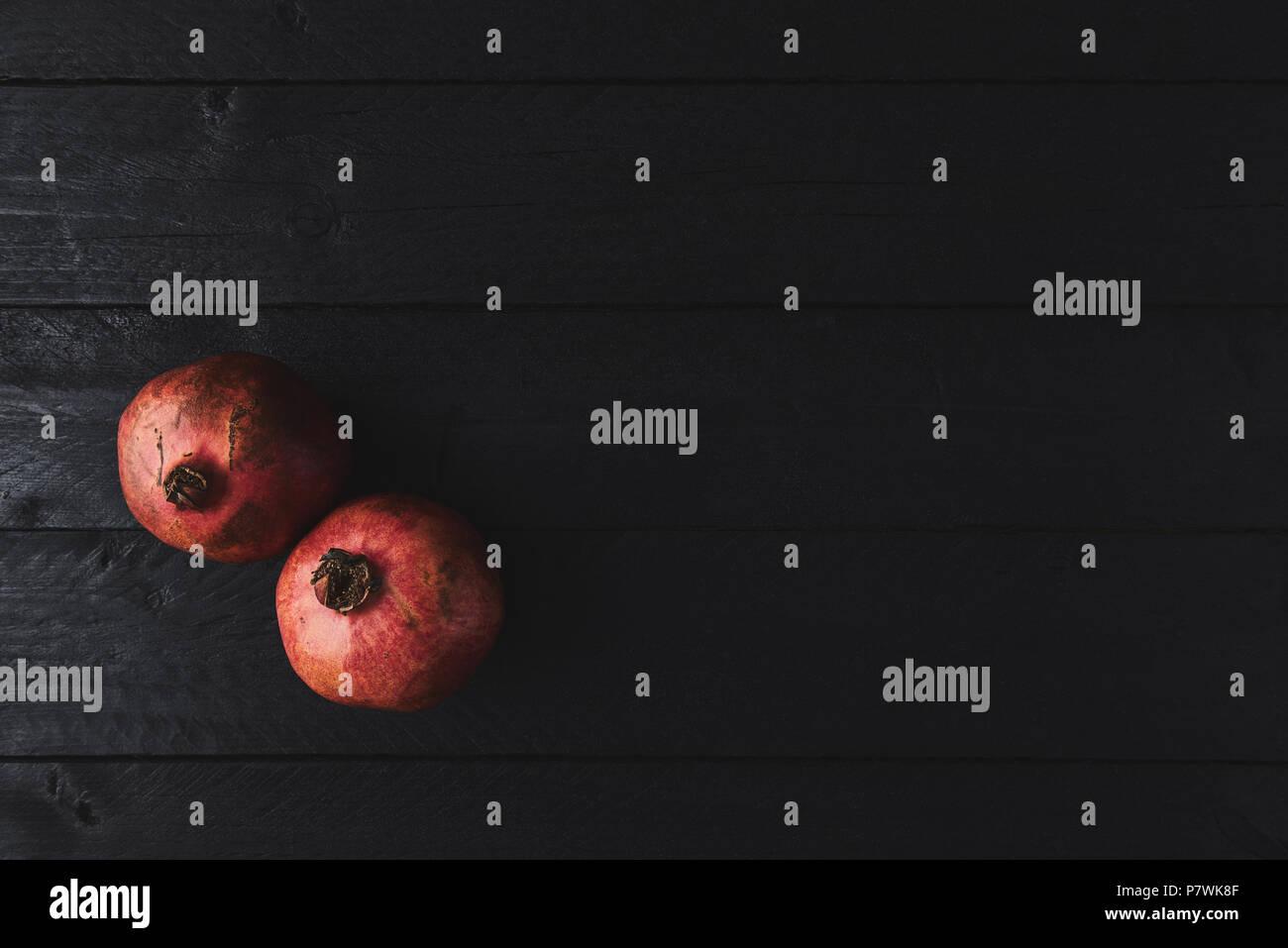 Mise à plat de fruits mûrs grenadier sur fond vintage en bois noir. Vue de dessus avec l'exemplaire de l'espace. Photo Stock