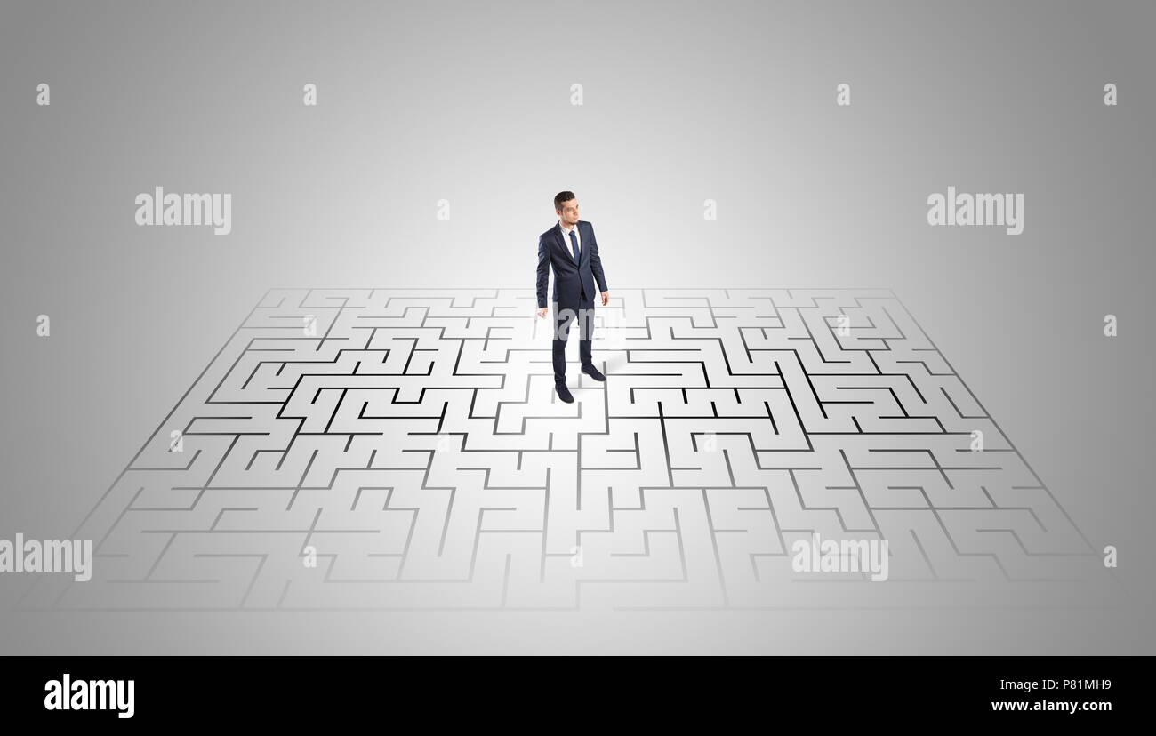 Homme élégant à la recherche d'une solution dans un milieu d'un labyrinthe Photo Stock