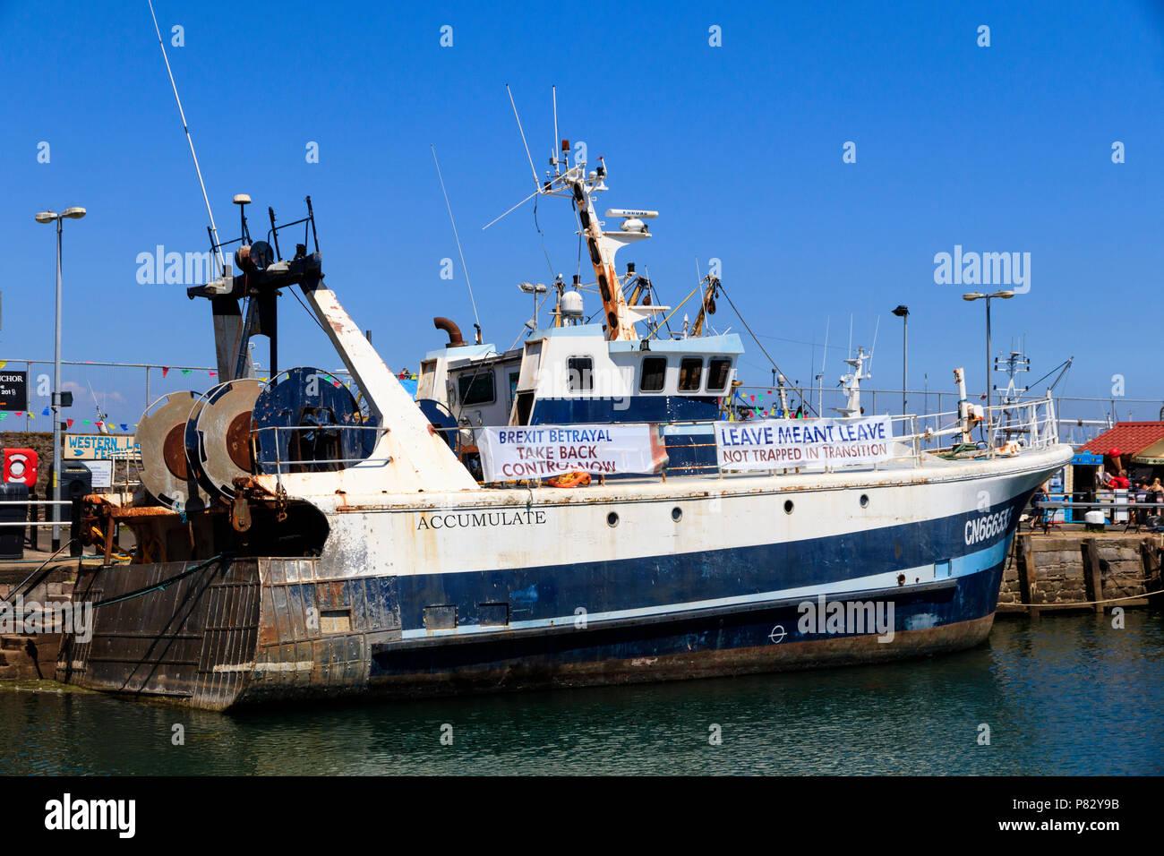 Chalutier en mer s'accumuler l'exécution Brexit banderoles de pêche dans le port de Brixham, Devon, UK Banque D'Images