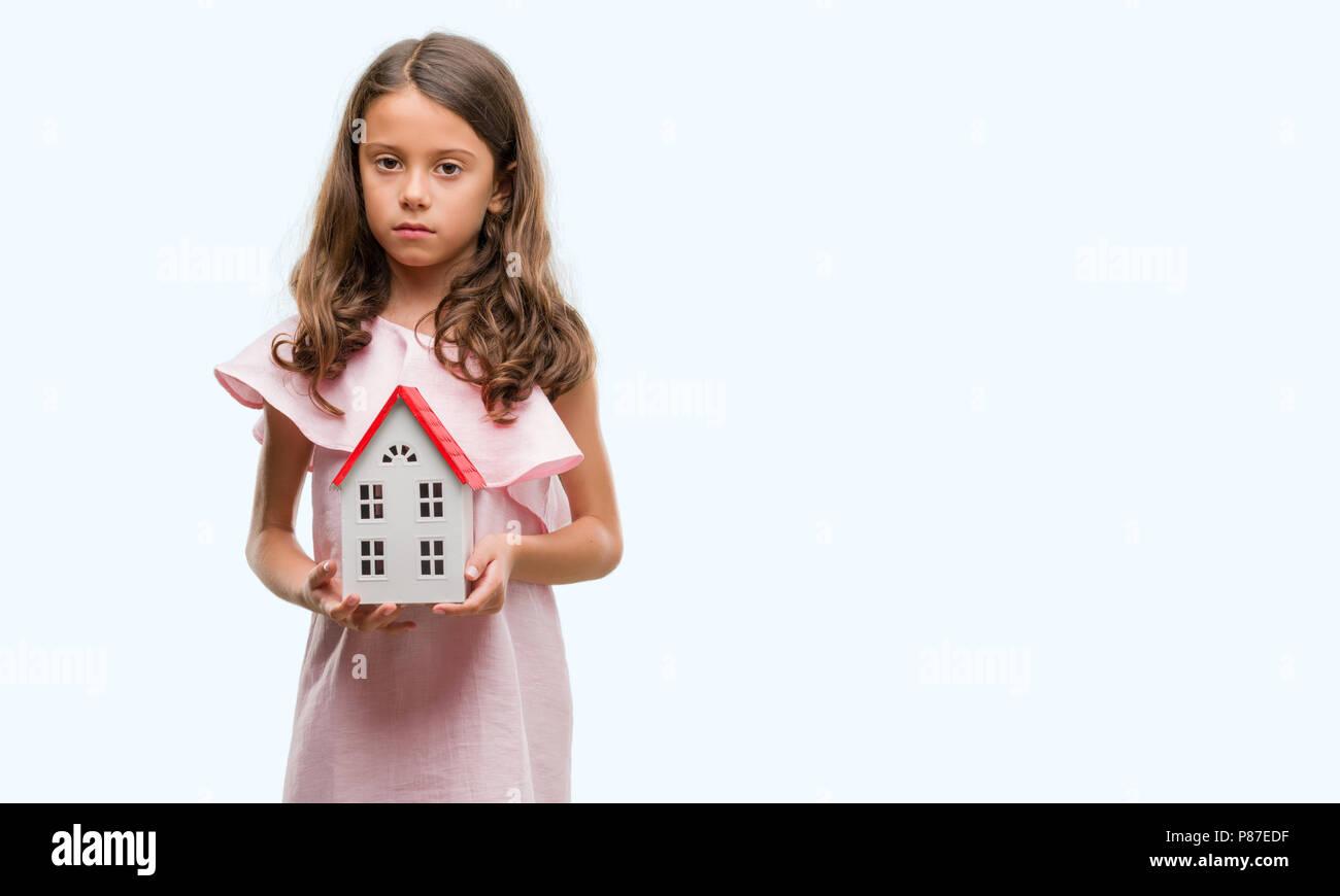 Brunette woman holding petite maison avec une expression confiante face à la pensée intelligente grave Banque D'Images