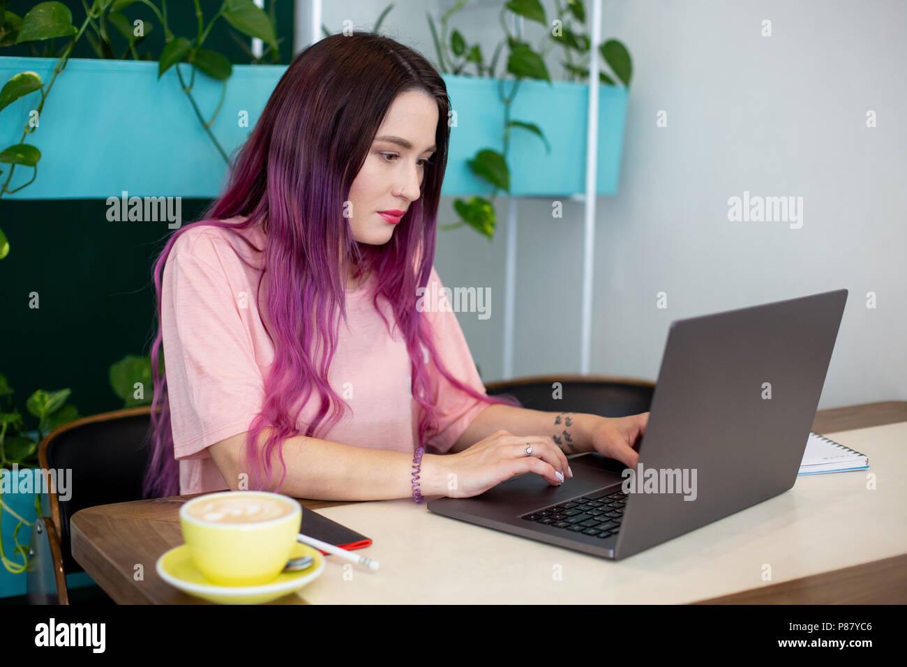 Jeune femme aux cheveux roses avec un ordinateur portable assis dans un café, une femme intelligente student working on net-book. Photo Stock