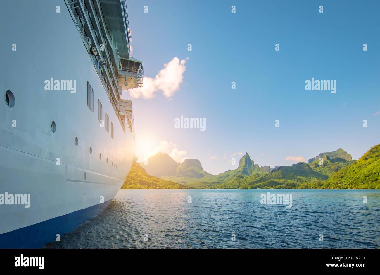 Vue de côté de l'ancre bateau de croisière au coucher du soleil. Arrière-plan la montagne. Photo Stock