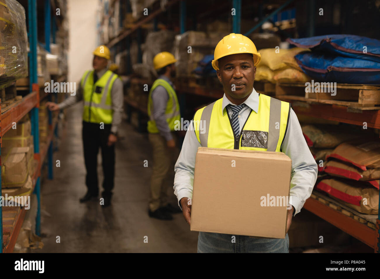 Le personnel masculin holding cardboard box in warehouse Photo Stock
