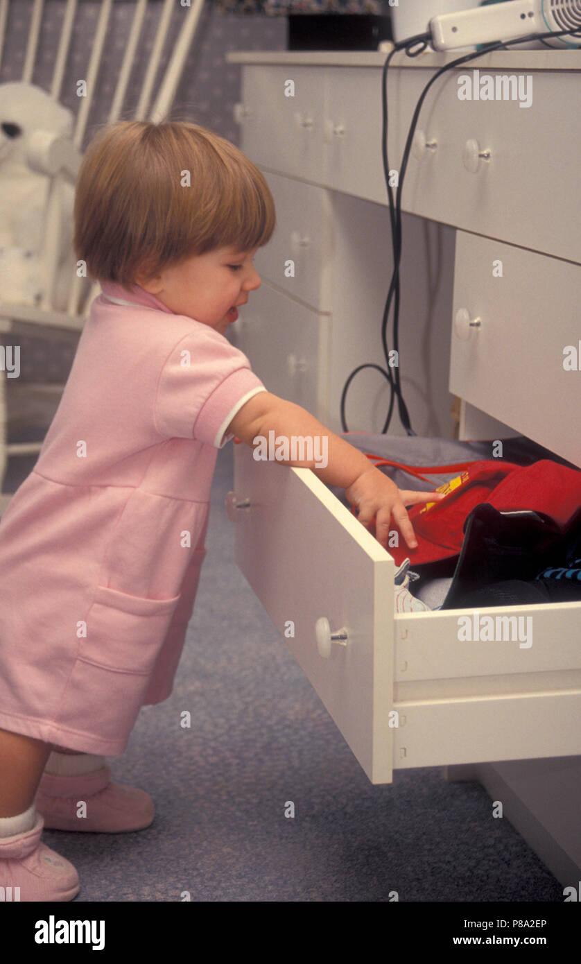 Enfant en tirant les choses hors de tiroir dans danger d'accident avec un sèche-cheveux Photo Stock