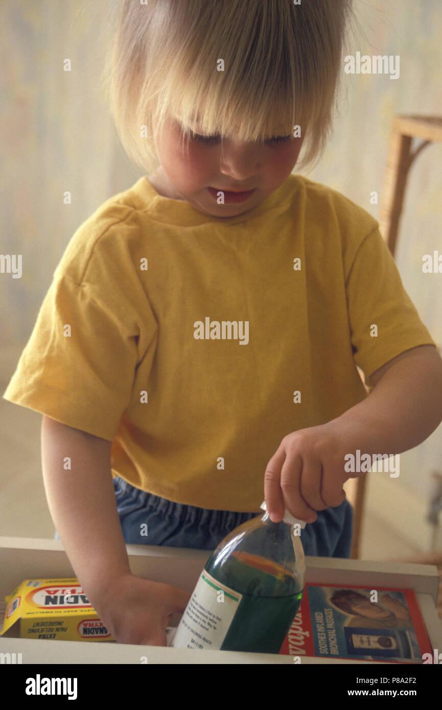 Enfant en tirant sur les médicaments hors des tiroirs Photo Stock