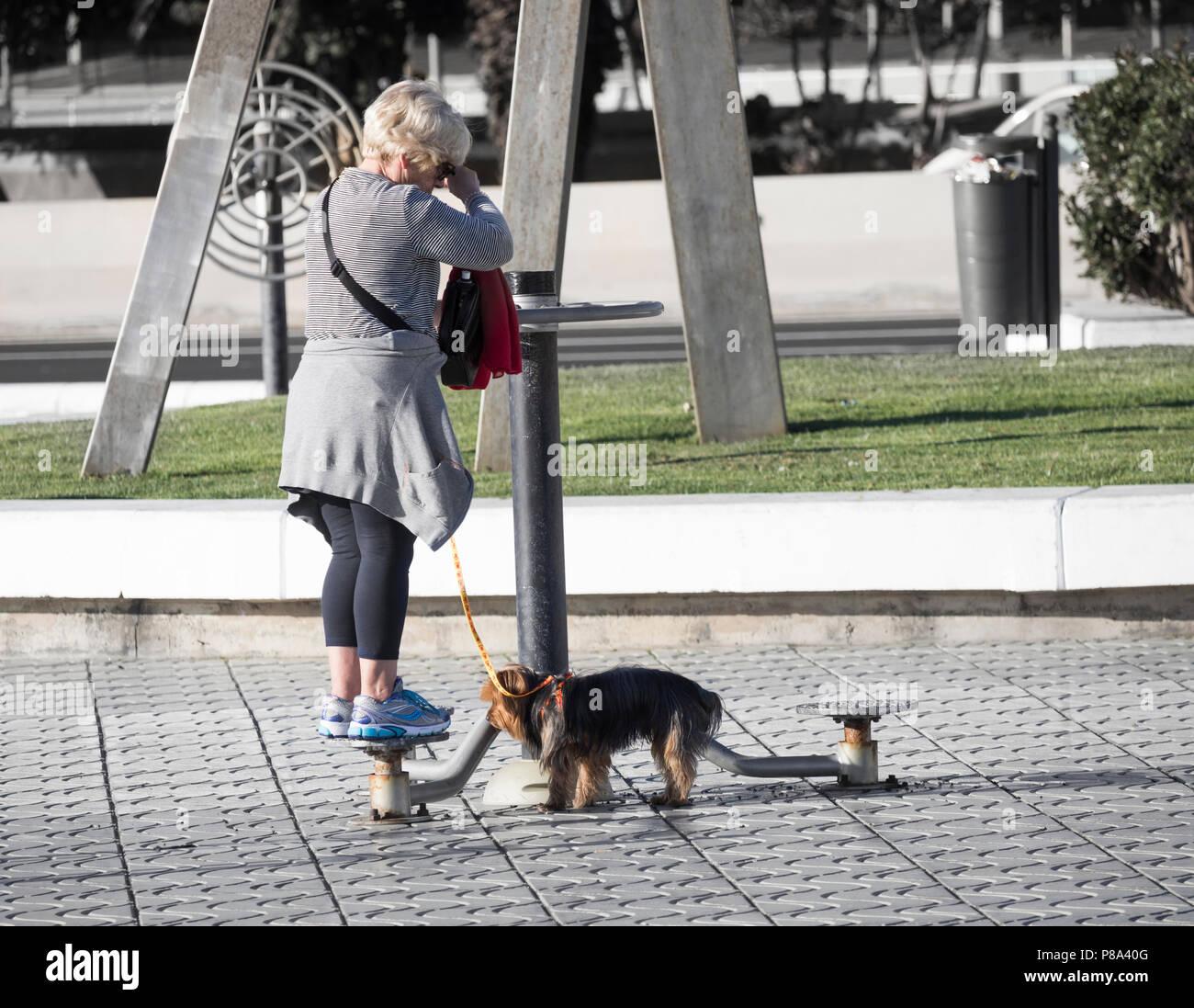 Personnes âgées woman walking dog en utilisant l'exercice à l'extérieur sur rue de ville en Espagne Photo Stock