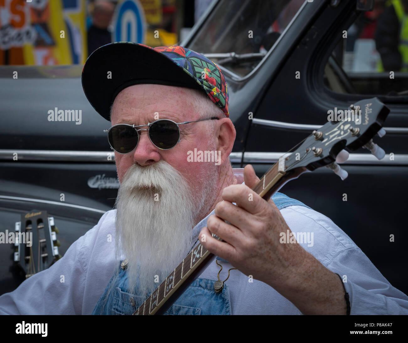 Homme avec une longue barbe et moustache barbiche jouant du banjo. Photo Stock