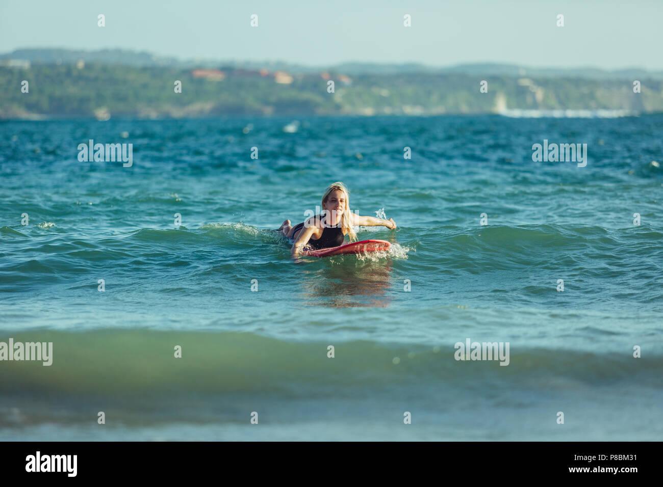 Belle piscine sportive sur une planche de surf dans l'eau Photo Stock