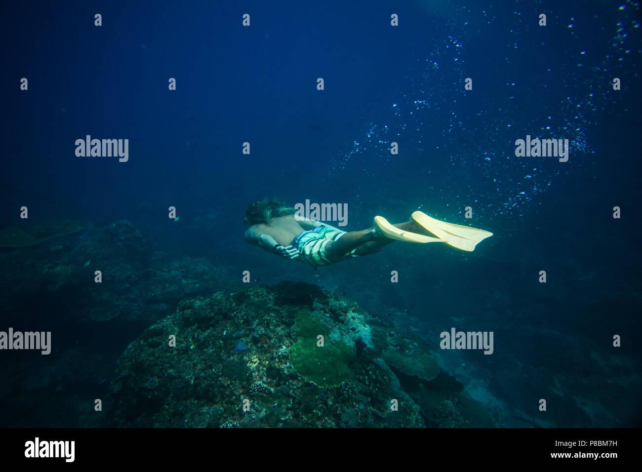 Vue de côté de l'homme à palmes de plongée dans le seul océan Photo Stock