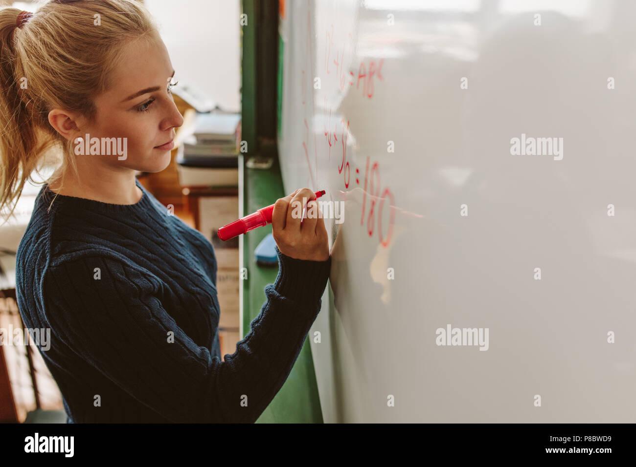 Close up of female student écrit une équation sur un tableau blanc dans la classe. L'écriture de fille à bord pendant les cours de maths. Photo Stock