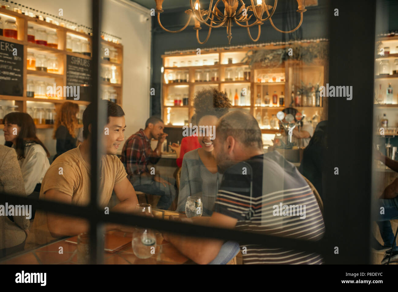 Smiling young friends sitting in a bar boissons ayant réuni Photo Stock