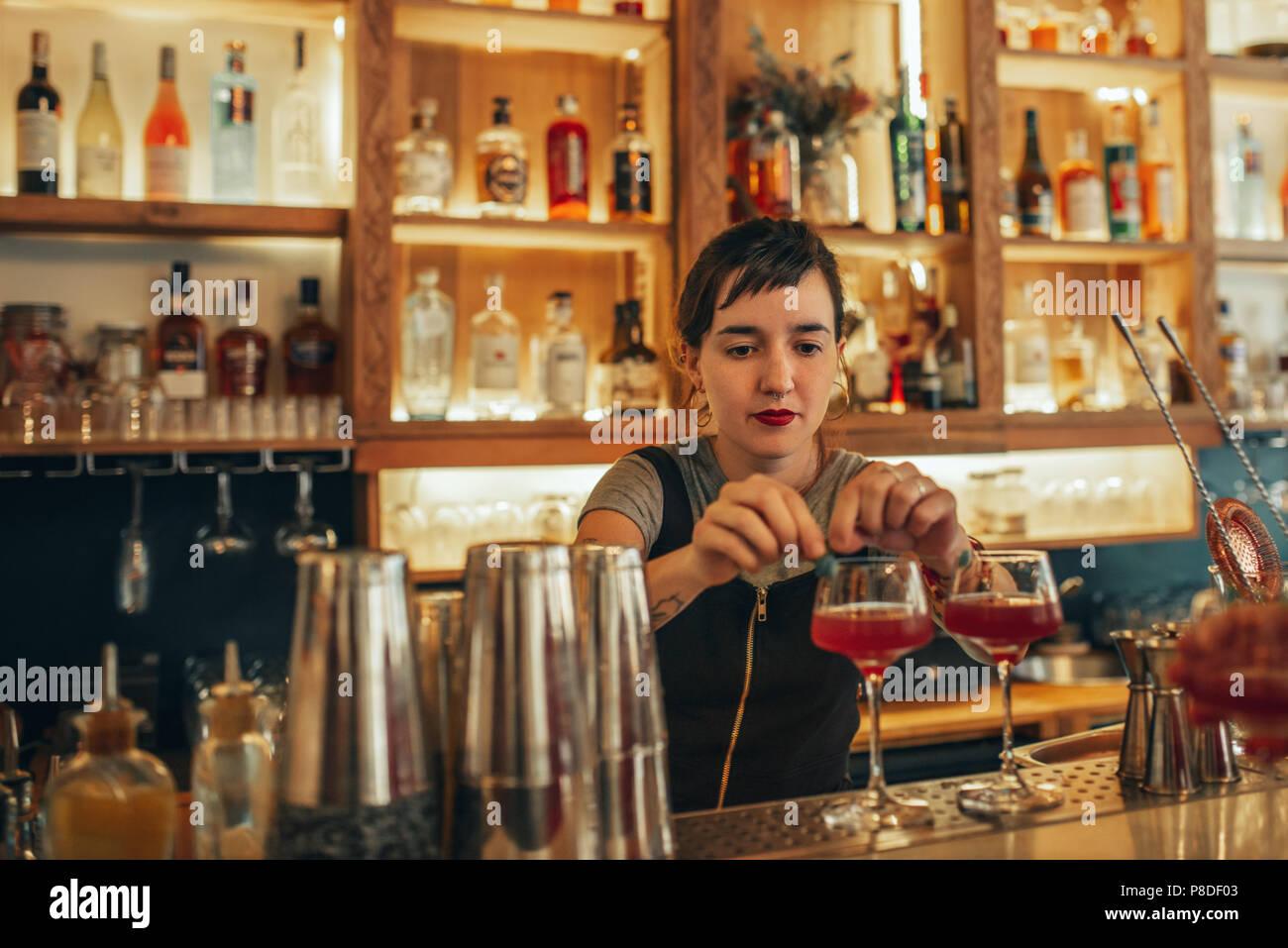 Young female bartender debout derrière un comptoir bar making cocktails Photo Stock
