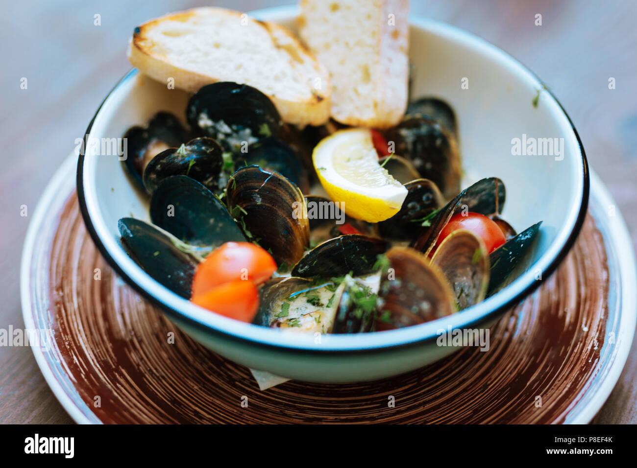Focus sélectif de moules au citron et tomates cerises Photo Stock