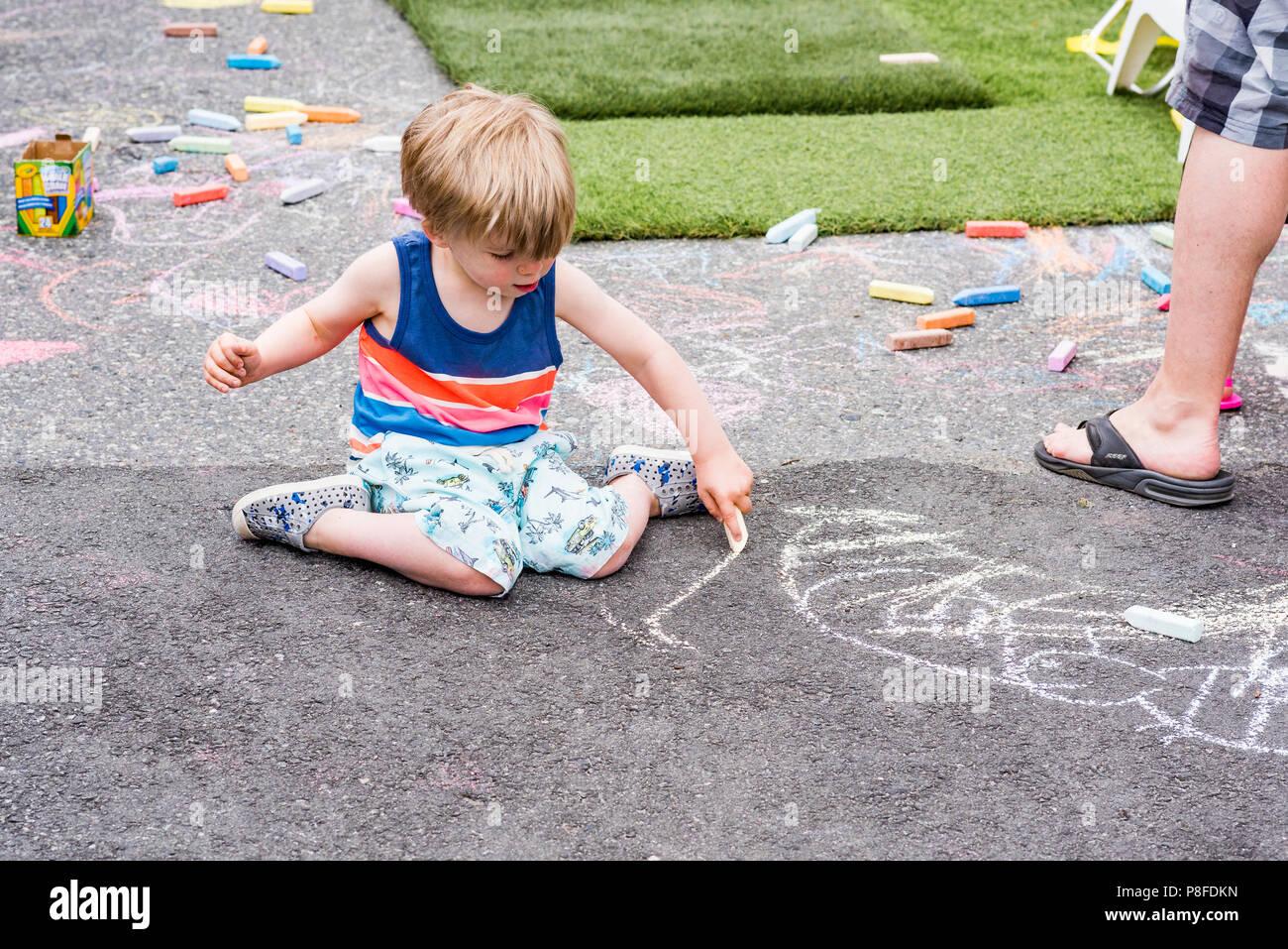 Jeune garçon faisant dessin à la craie sur le trottoir Banque D'Images