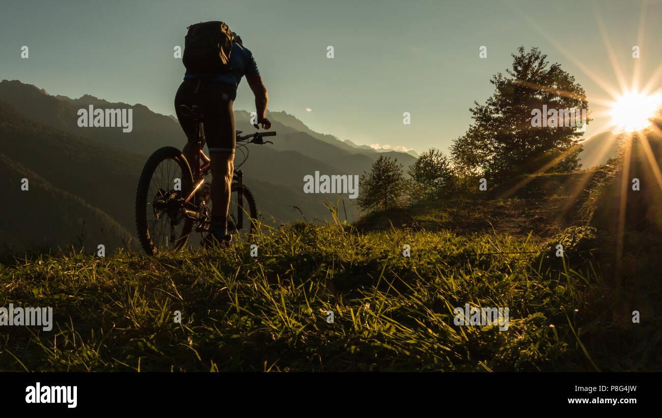 Un homme biker sur son vélo VTT au coucher du soleil dans les montagnes des Dolomites Alpes de l'Italie Photo Stock
