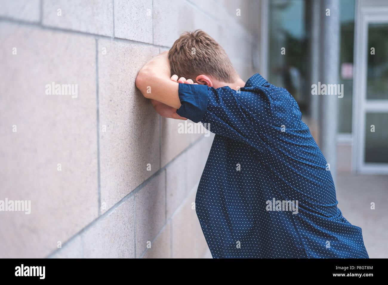 Pleurer dans l'adolescence, les bras croisés contre un mur de briques. Photo Stock