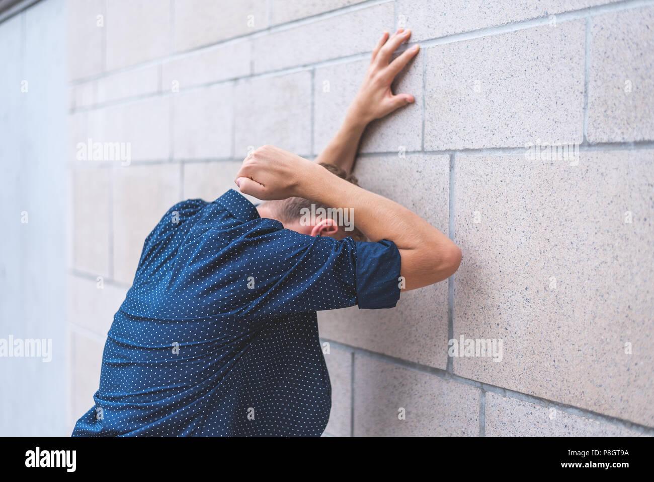 Mur de briques de frappe de l'adolescence dans la frustration. Photo Stock