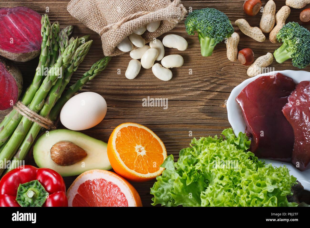 Les sources naturelles d'acide folique comme foie, asperges, brocoli, oeufs, salade, avocat, paprika, noix, fèves et épluchés , orange Photo Stock