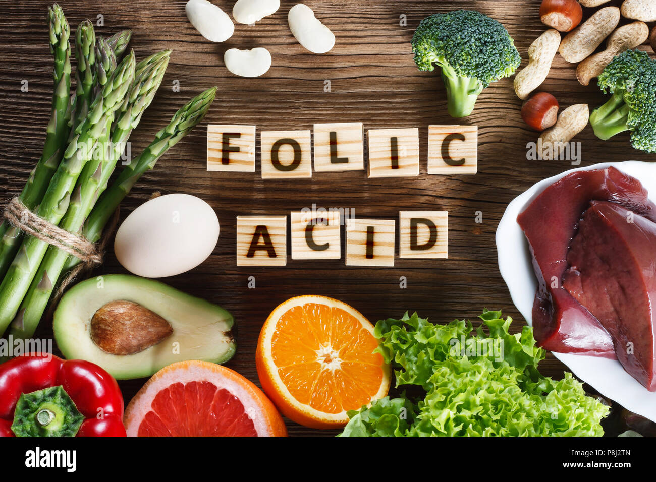 Les sources naturelles d'acide folique comme foie, asperges, brocoli, oeufs, salade, avocat, de paprika, de noix, d'orange, de betterave et de haricots Photo Stock