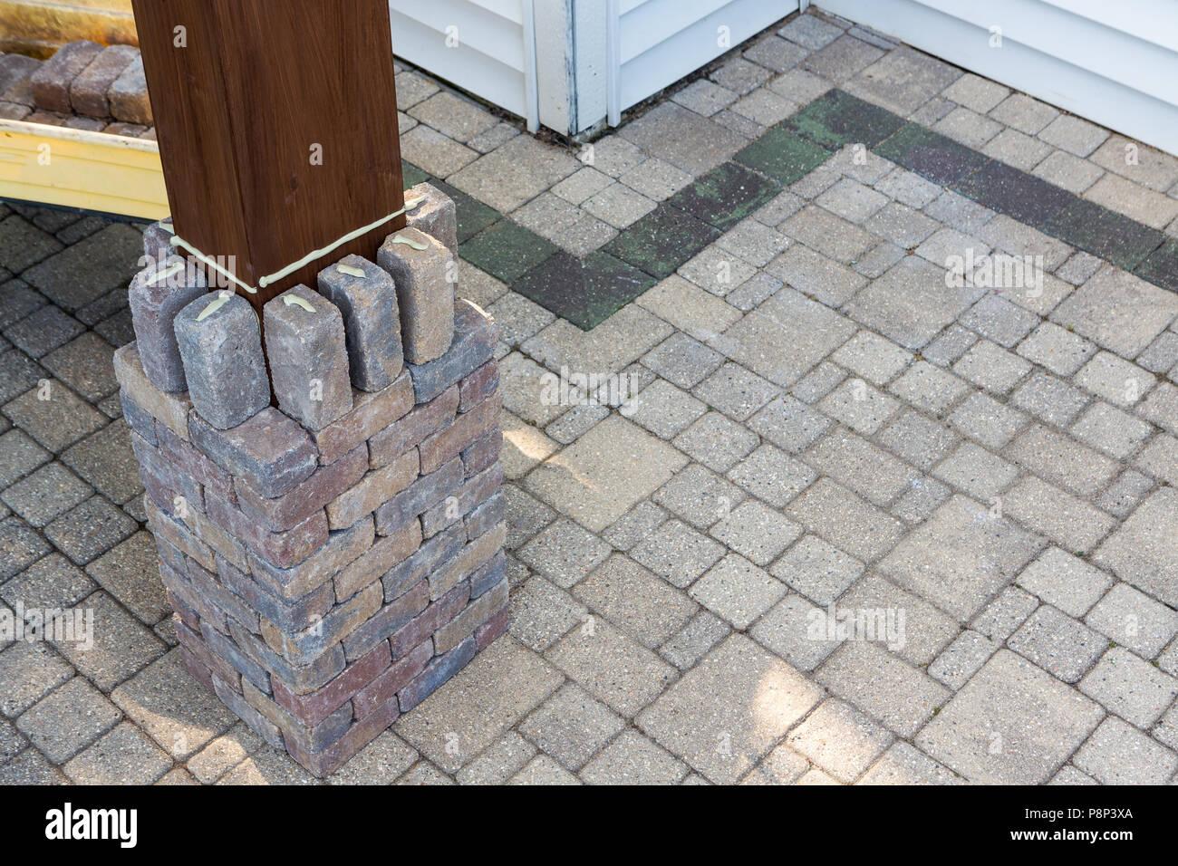 la construction d'un pilier en brique autour d'un collage de la