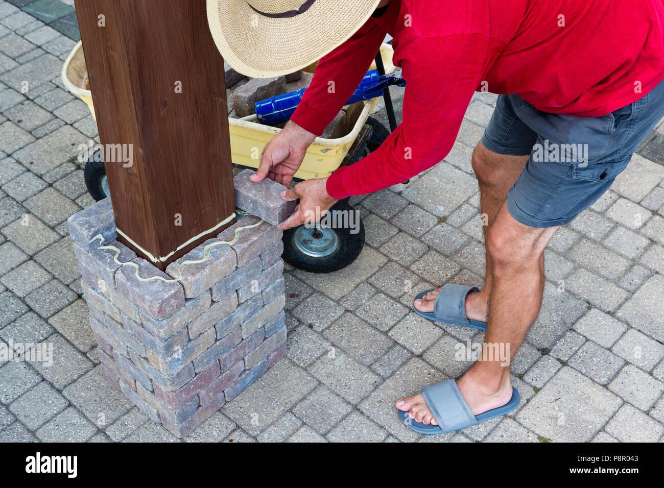 l'encollage des briques gris homme autour d'un gazebo en bois de la
