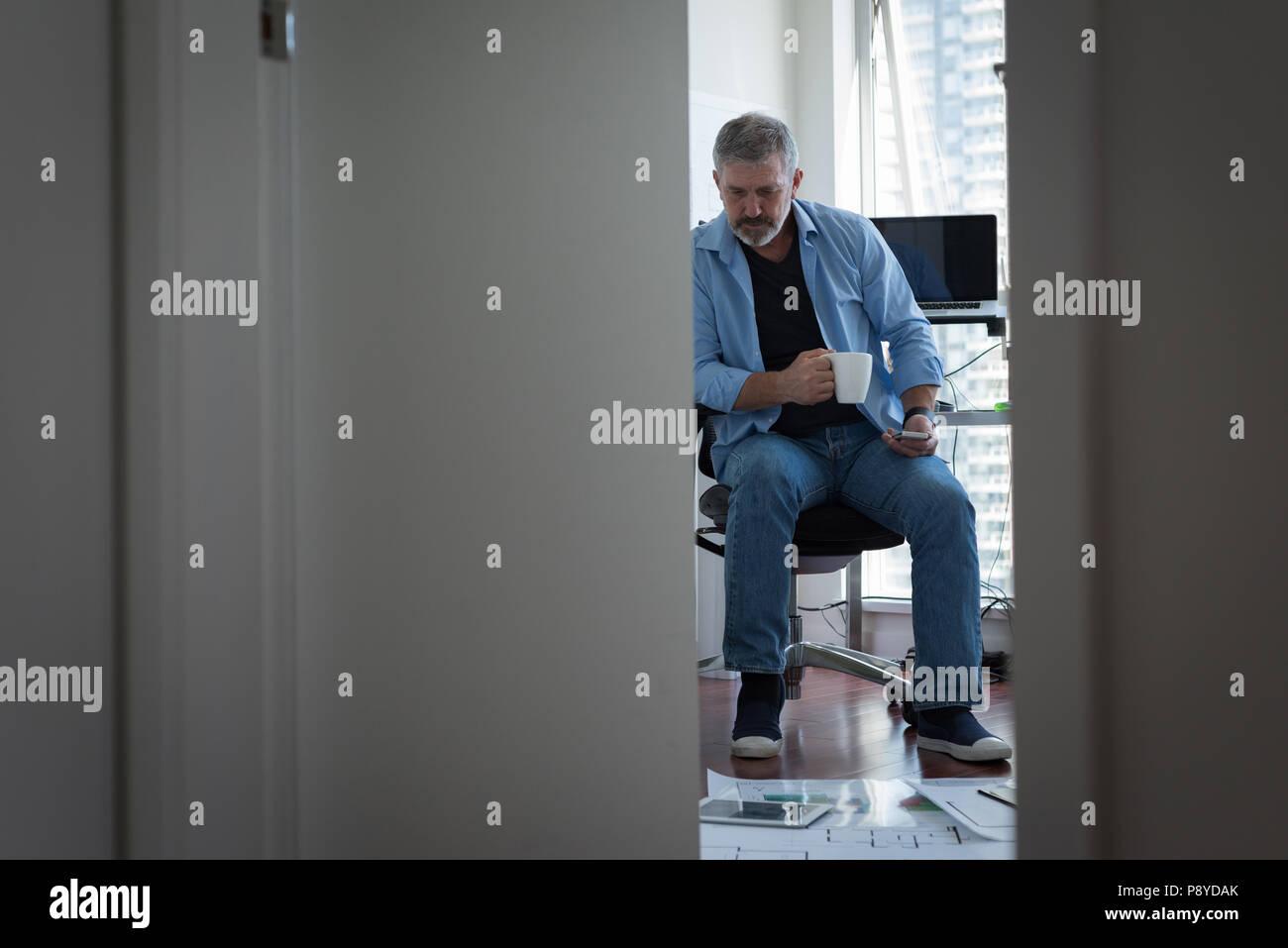 L'homme le café tout en travaillant à la maison Photo Stock