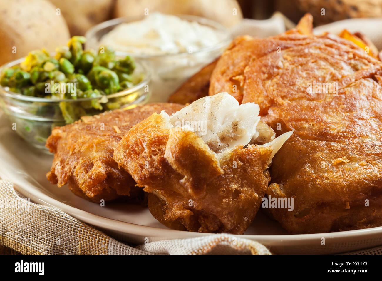 Le poisson dans la pâte traditionnelle de la bière et des frites avec de petits pois et sauce tartare Photo Stock