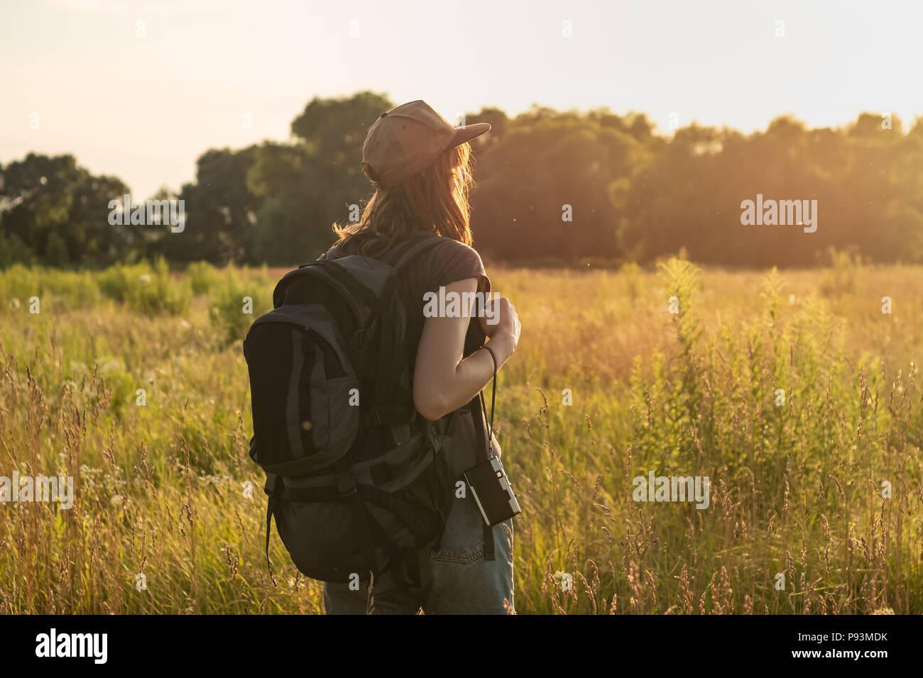 Jeune femme avec sac à dos dans la zone touristique. Personne de sexe féminin à la recherche au coucher du soleil dans l'herbe haute de la belle région rurale en été Banque D'Images