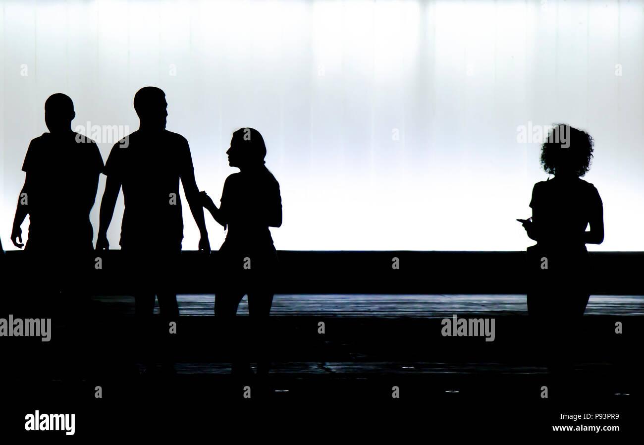 Silhouettes floues de trois jeunes amis étudiants et un garçon est à la recherche d'une nouvelle fille avec des cheveux bouclés tout seul dans le noir et blanc de nuit Banque D'Images
