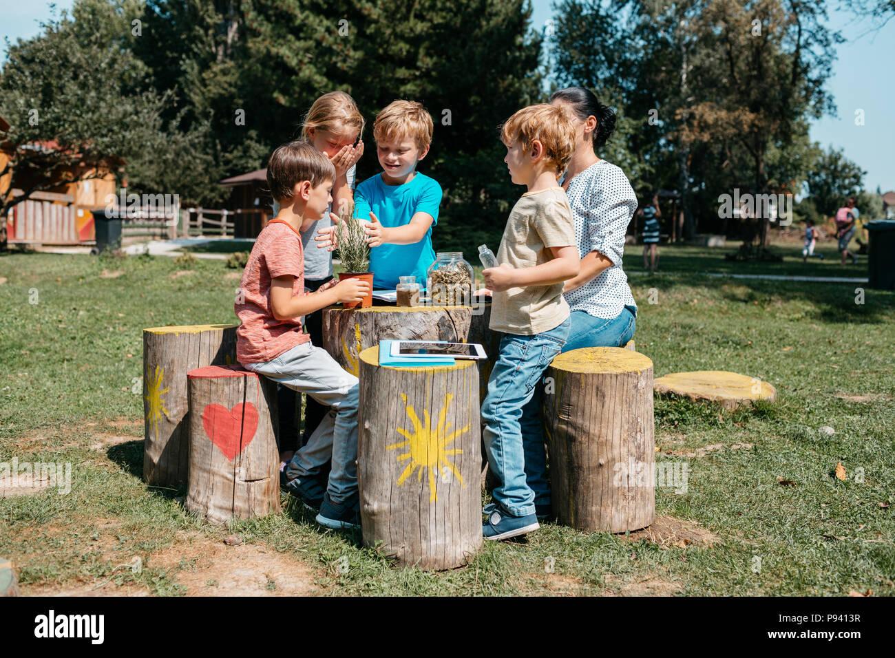 Groupe de jeunes écoliers ayant une leçon en extérieur dans un parc. Les jeunes élèves du primaire à la découverte des herbes à travers leurs sens dans un jardin. Photo Stock