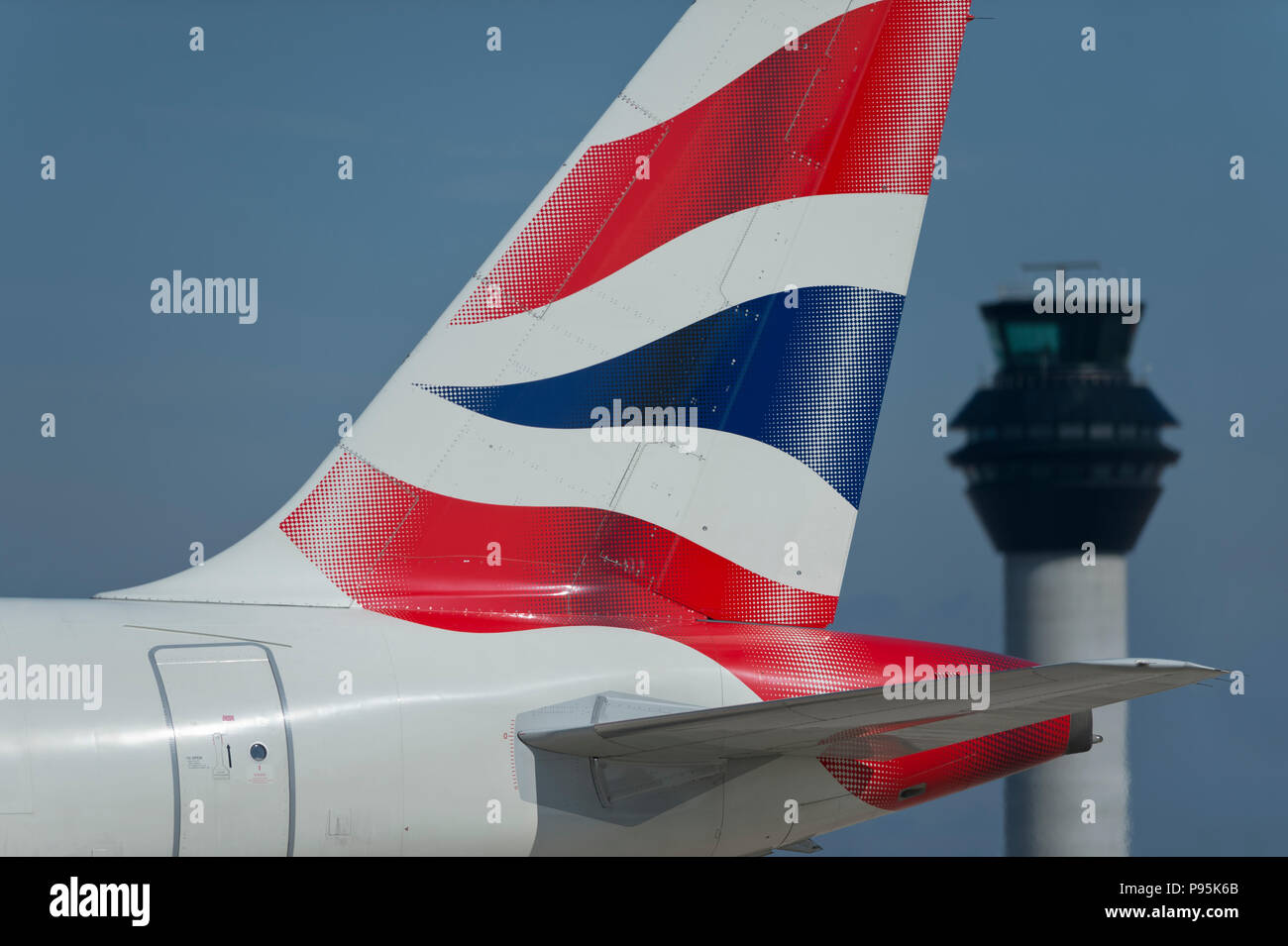 La tailfin d'un British Airways Airbus A319-131 circule le long de la piste en face de la tour de contrôle à l'aéroport de Manchester. Photo Stock