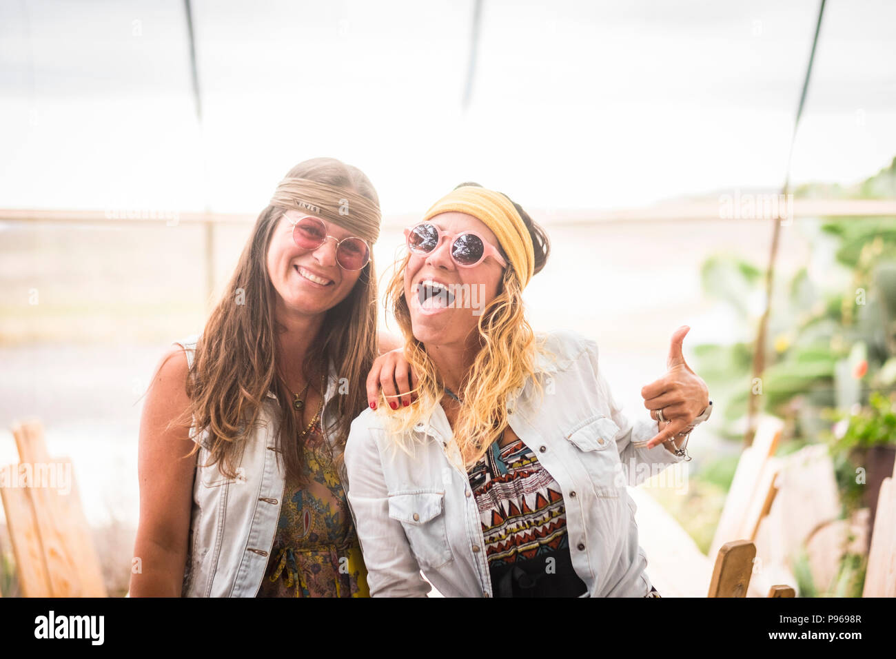 Couple de femelles fou amis s'amuser et profiter de port vieux hippie style retro style Vêtements et accessoires. la mode et de l'amitié pour les jeunes c Photo Stock