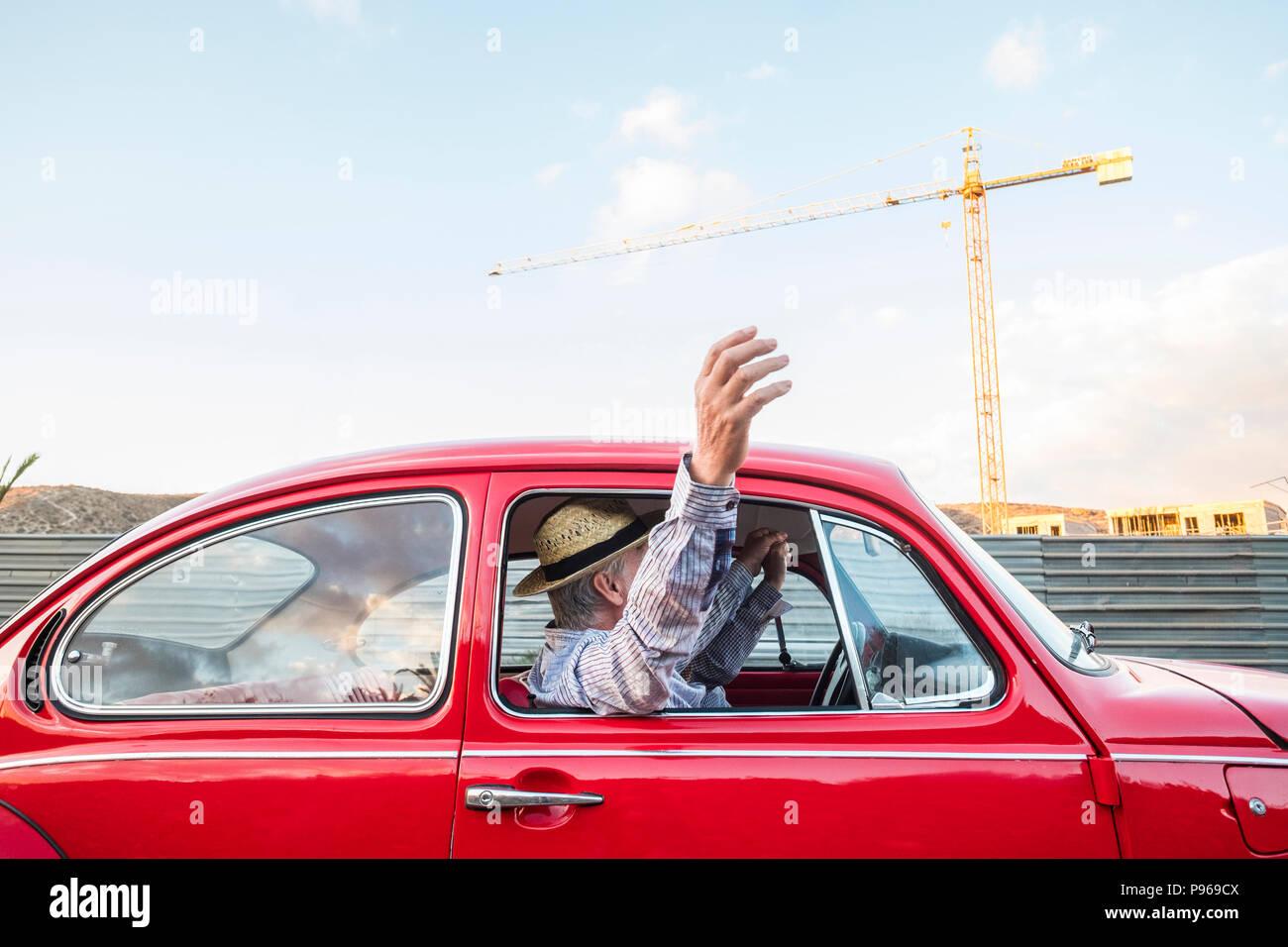 Portrait d'âge mûr et de voyage en voiture sur une voiture vintage rouge. Locations et wonderlust concpet pour gens heureux déménagement partout dans le monde de la construction. Banque D'Images
