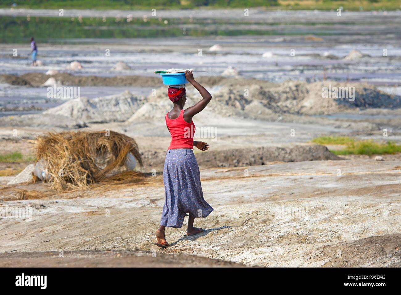 African Woman Walking transportant sur la tête de bassin, l'Afrique femme porte la charge au dessus de sa tête, de l'Ouganda Photo Stock