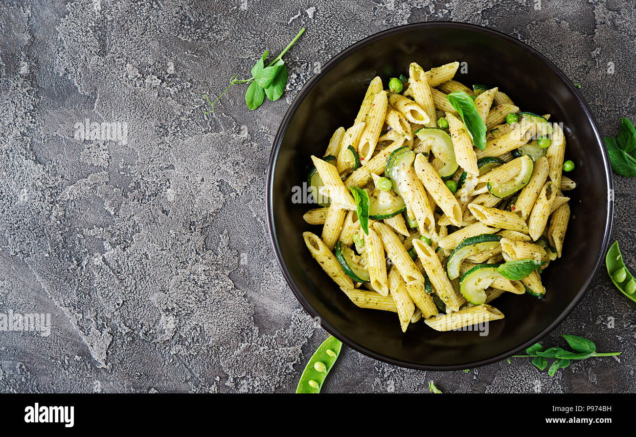 Pâtes penne au pesto, courgettes, pois verts et basilic. Cuisine italienne. Vue d'en haut. Mise à plat. Photo Stock