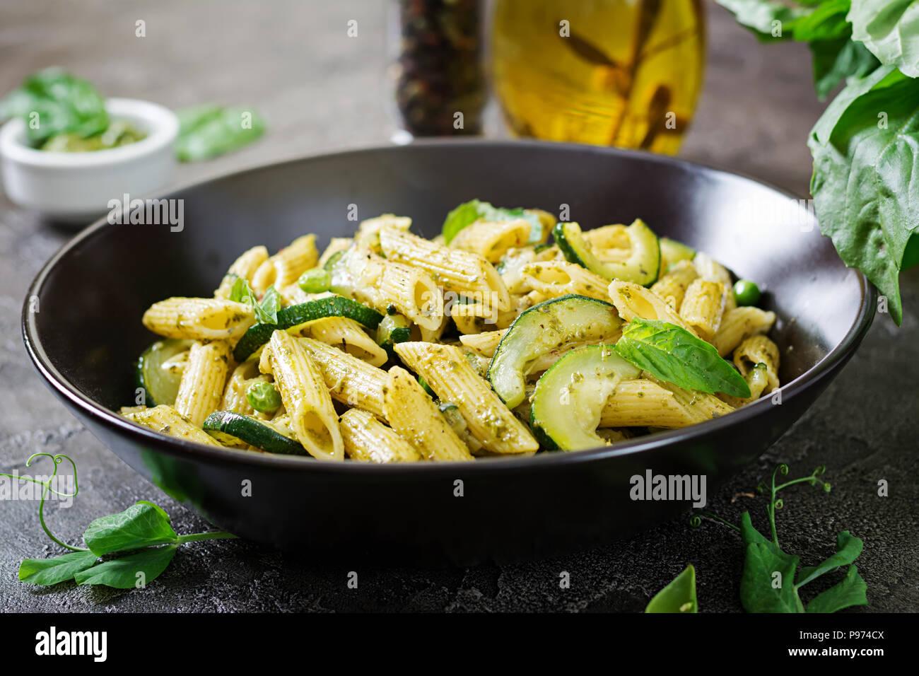 Pâtes penne au pesto, courgettes, pois verts et basilic. Cuisine italienne. Photo Stock