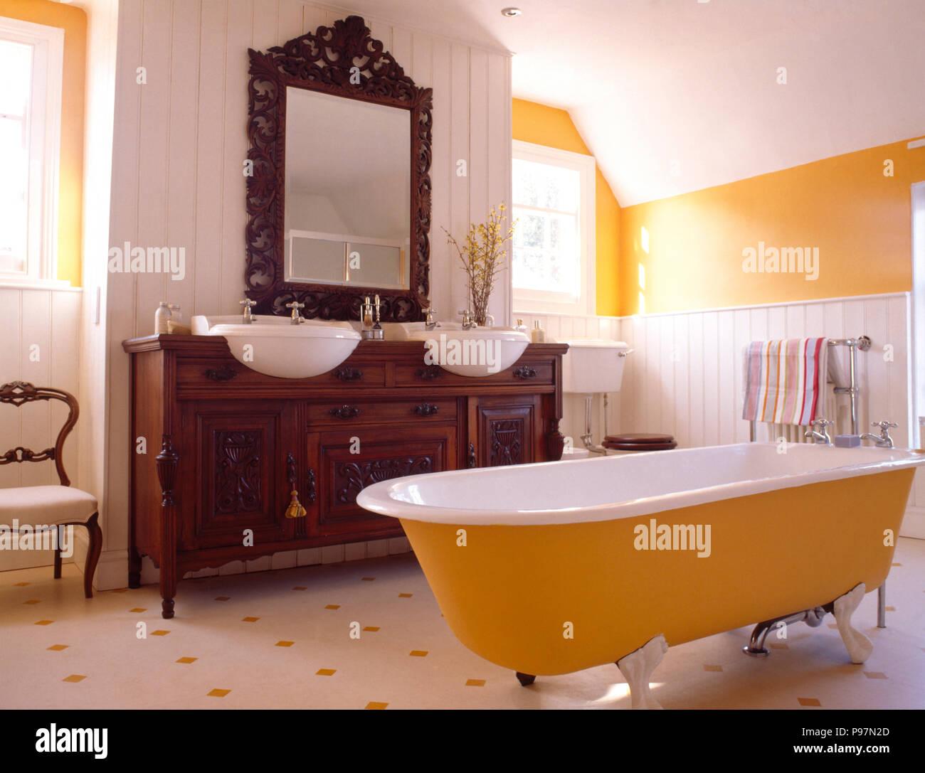 Baignoire Jaune Jaune Et Blanc Dans Une Salle De Bains Privative Avec Un  Miroir Au Dessus Du0027un Placard Encastré Avec Deux Vasques