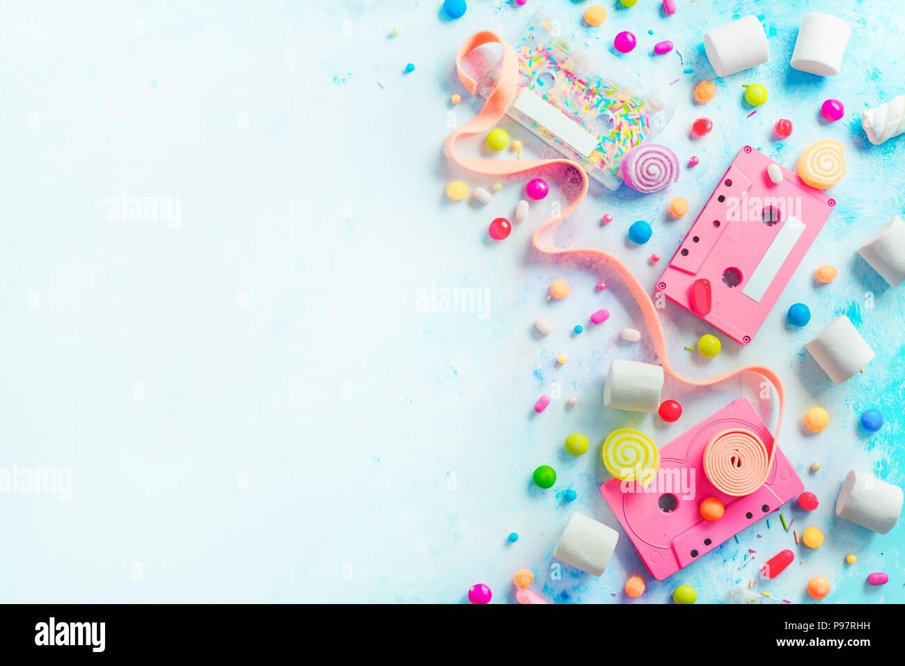 Cassettes rose dans une douce mélodie concept. Bonbons, arrose et marmelades sur fond clair avec l'exemplaire de l'espace. Télévision couleur pastel en-tête laïcs Banque D'Images