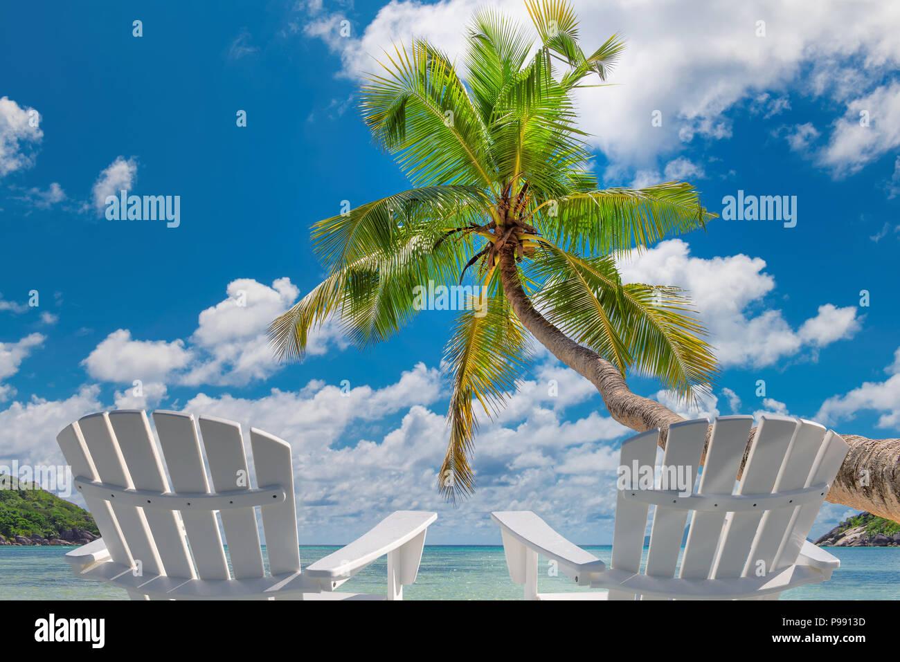 Chaises de plage sur la plage de sable fin avec palmiers et mer turquoise. Photo Stock