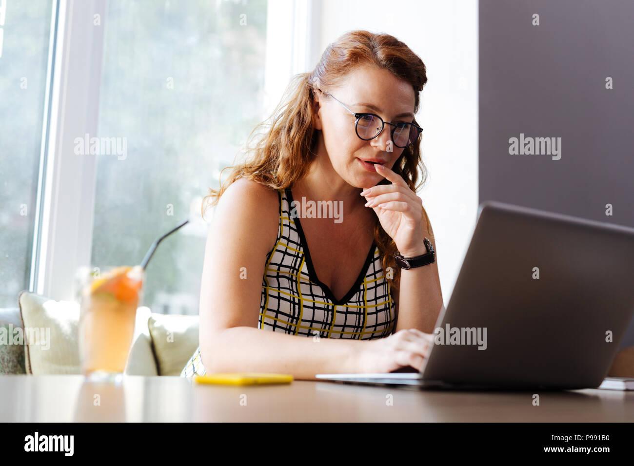 Belle rousse femme travailleur à distance sentiment réfléchi Photo Stock