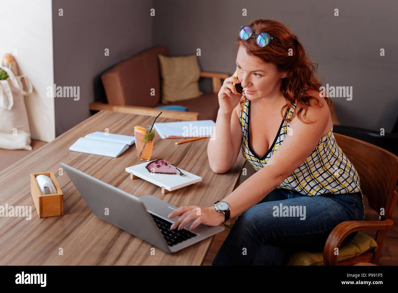 Femme d'appeler son collègue occupé tout en ayant des salles Photo Stock