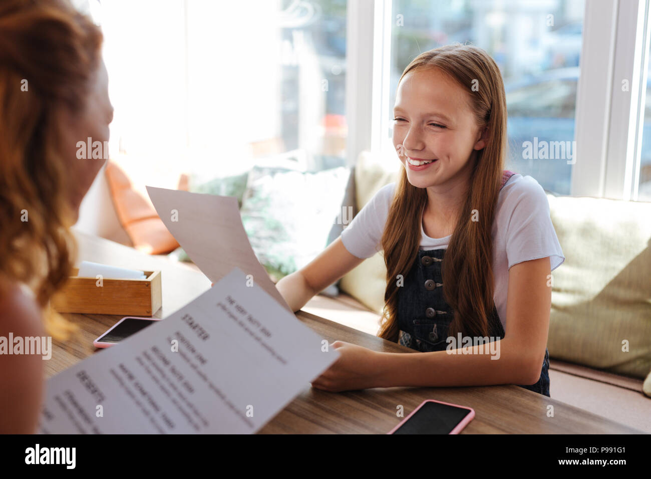 Blonde-haired girl smiling tout en choisissant le menu de plats Photo Stock