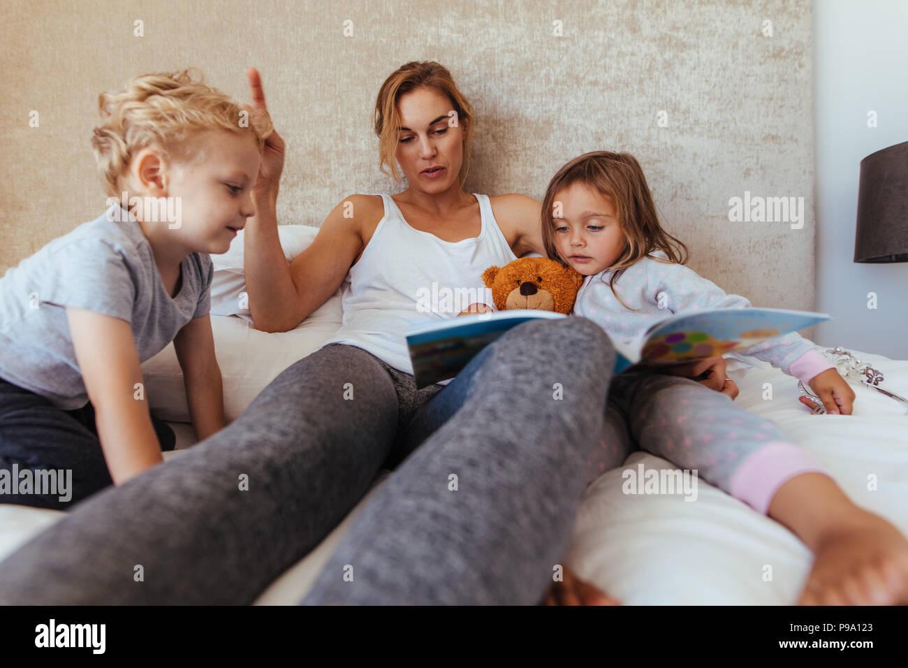 Histoire avant la lecture de la mère aux enfants à la maison. Mère attentive lecture du livre pour enfants sur l'adorable petit lit. Photo Stock