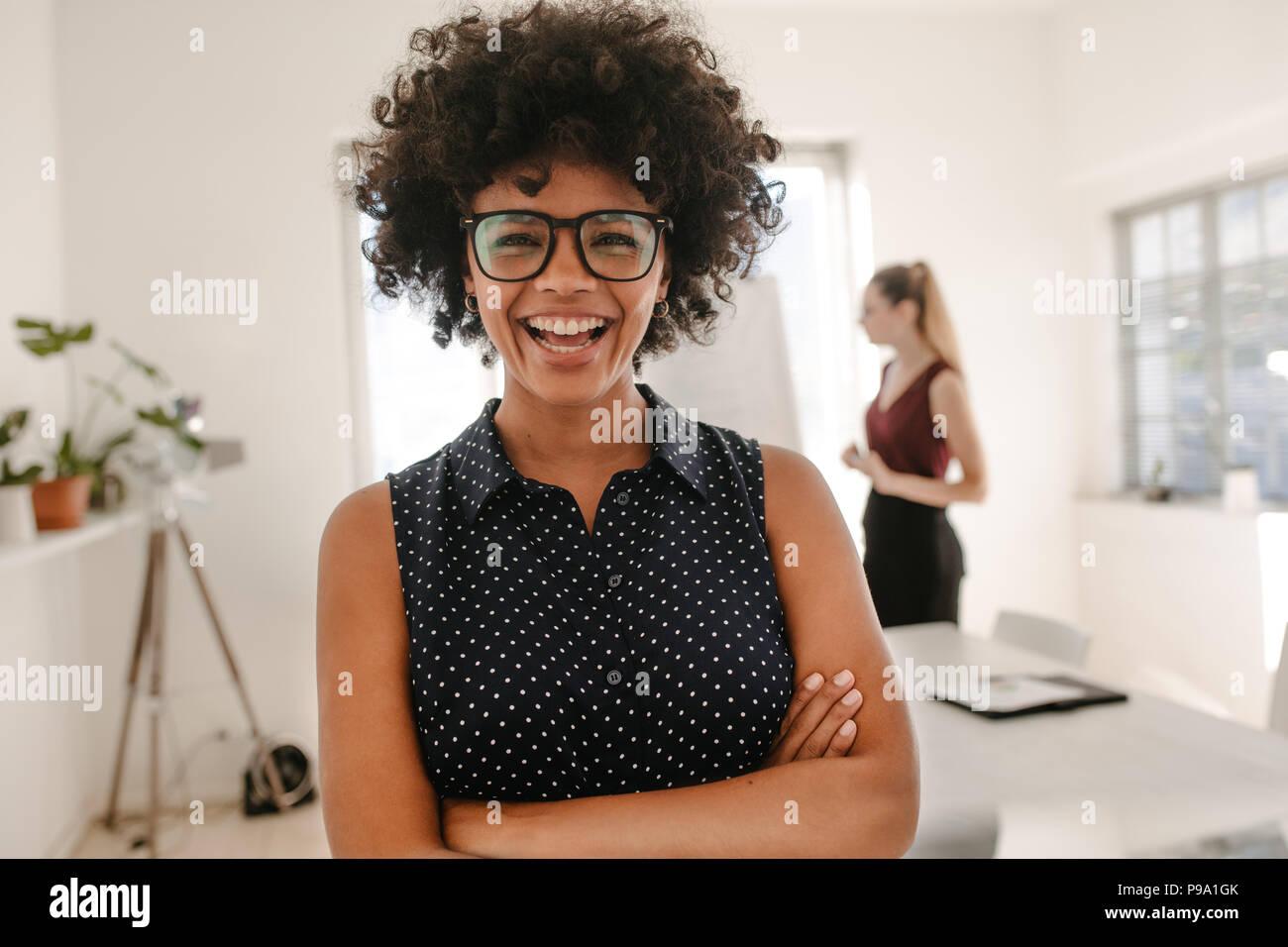 Portrait of young African woman les bras croisés dans la salle de réunion avec son collègue la presentation en arrière-plan. Femme laughin Banque D'Images