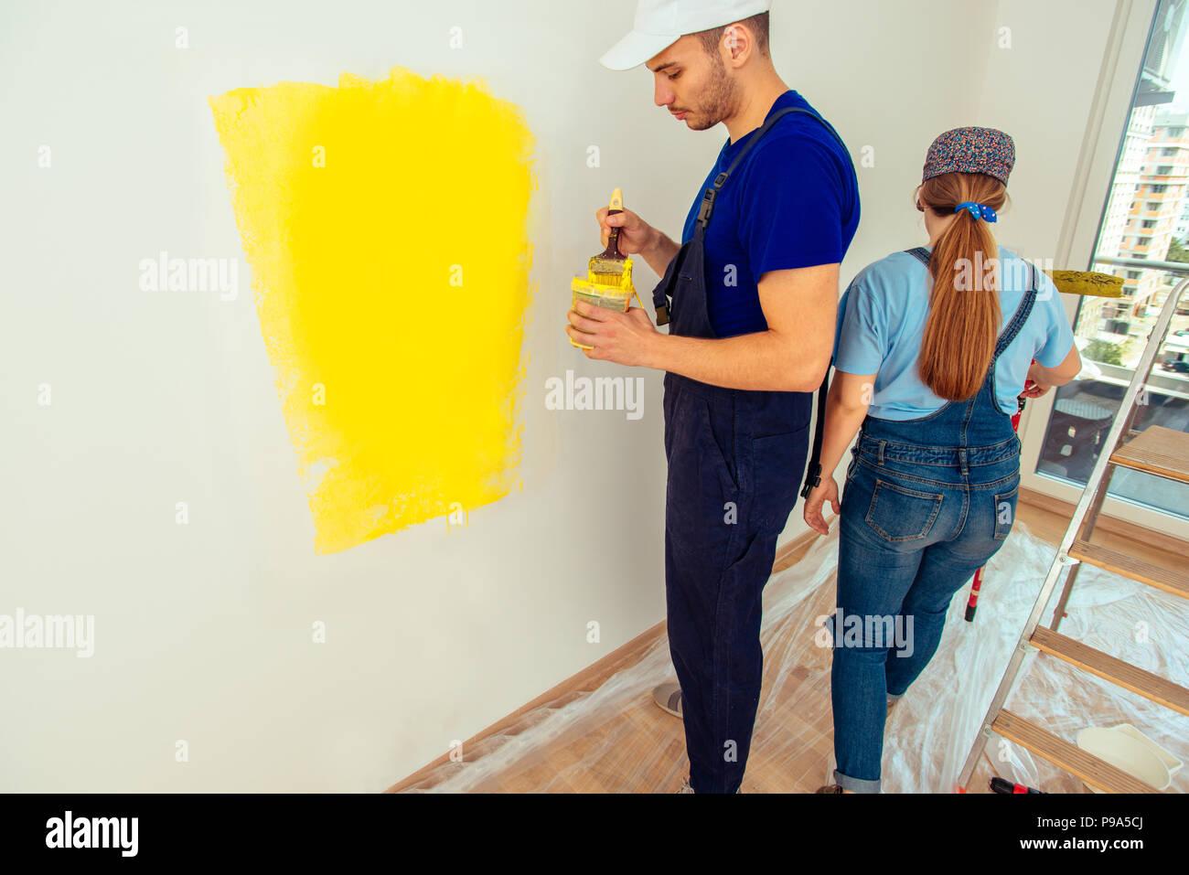 Jeune Couple En Salopette De Travail Mur Peinture En Jaune