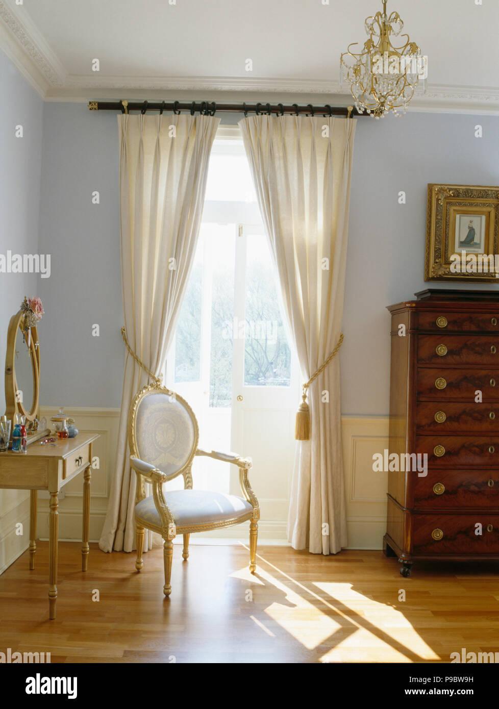 Rideaux crème à portes-fenêtres dans une chambre bleu pastel Banque ...