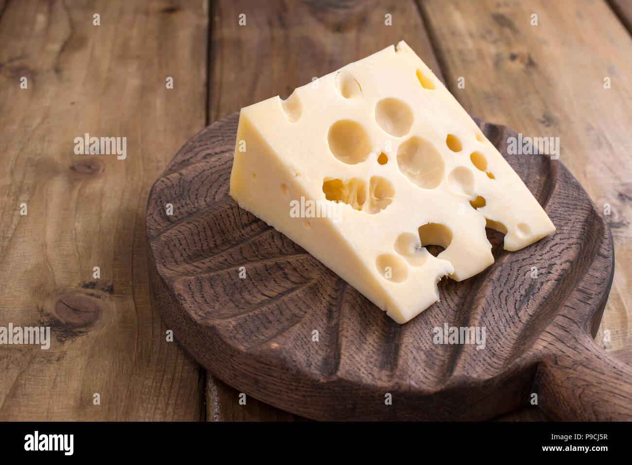 Fromage avec des trous sur une vieille planche en bois. Vintage photo. Les produits laitiers. Espace libre pour le texte. Copy space Photo Stock