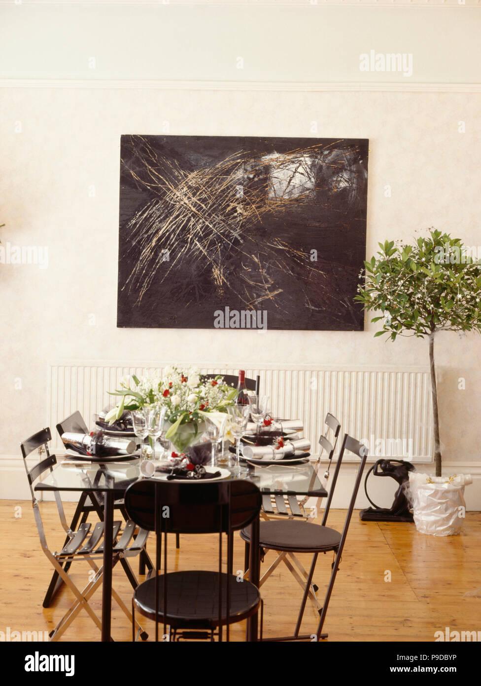 Chaises Et Table En Verre Noir Fixé Pour Le Dîner De Noël Dans La Salle à  Manger Moderne Blanc Avec La Peinture Abstraite, Au Dessus De Bay Tree En  Pot ...