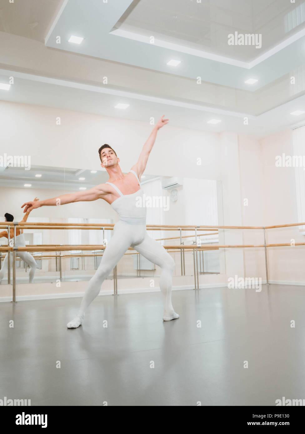 Jeune beau danseur pratiquant dans le ballet classique en petit studio avec miroirs. L'homme en collants blancs. Chorégraphe professionnel travaille sur la création de la performance. Photo Stock