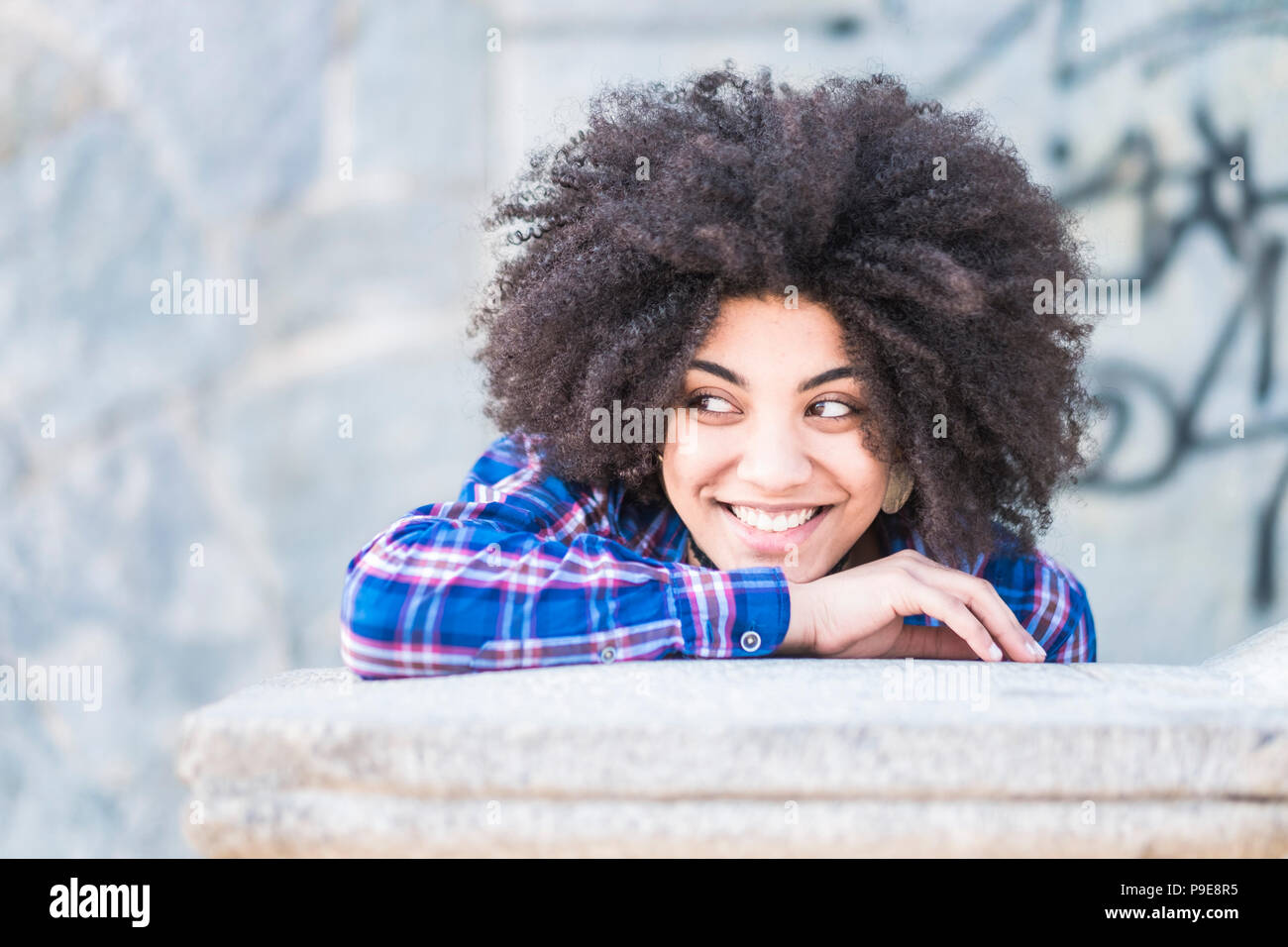 Portrait de race africaine de la peau noire de belle jeune fille souriant et à la recherche à ses côtés. Profitant de l'heure et l'activité de loisirs. Ambiance décontractée et fa Banque D'Images
